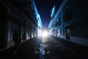 A woman walks down a darkened street past historic buildings in the touristic Old San Juan neighborhood, on October 13, 2017 in San Juan, Puerto Rico. (Credit: Mario Tama/Getty Images)