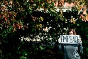 "A protester holds an ""impeach"" sign outside the Trump National Golf Course as a motorcade with US President Donald Trump arrives in Sterling, Virginia, on October 28, 2017. (Credit: Brendan Smialowski/AFP/Getty Images)"