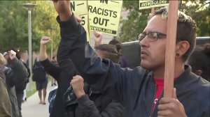 A student protests at Cal State Fullerton the arrival of speaker Milo Yiannopoulos, a controversial figure with a following of far-right conservatives, nativists and white supremacists. (Credit: KTLA)