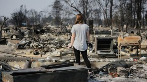 Margaret Curzon looks at the remains of her childhood home in Santa Rosa on Oct. 15, 2017, while holding the items of emotional importance she was able to salvage. (Credit: Elijah Nouvelage/Getty Images)