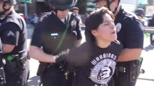 A young woman is taken into custody after dozens of protesters block traffic in Westwood as the deadline to renew DACA loomed on Oct. 5, 2017. (Credit: KTLA)