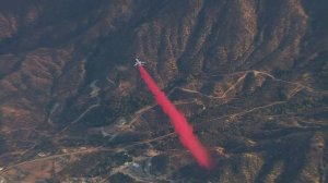 A DC-10 drops Phos-Chek at the edge of the Wildomar Fire on Oct. 26, 2017. (Credit: KTLA)