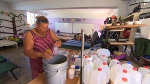 Margarita Cosme Fuentes washes dishes in the classroom serving as her temporary home in hurricane-devastated Puerto Rico in Oct. 2017. (Credit: CNN)