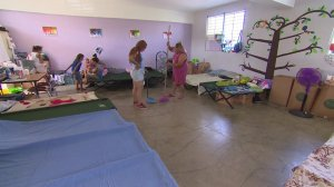 Margarita Cosme Fuentes, sweeps the floor of classroom serving as her temporary home in hurricane-devastated Puerto Rico in Oct. 2017. (Credit: CNN)