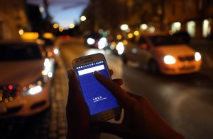 In this photo illustration, a woman uses the Uber app on Sept. 2, 2014, in Berlin, Germany. (Credit: Adam Berry / Getty Images)