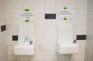 Placards posted above water fountains warn against drinking the water at Flint Northwestern High School in Flint, Michigan, May 4, 2016. (Credit: Jim Watson / AFP / Getty Images)