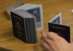 A Passport Processing employee uses a stack of blank passports to print a new one at the Miami Passport Agency on June 22, 2007. (Credit: Joe Raedle / Getty Images)