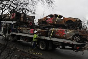 A worker secures burned-out cars onto a truck in the Coffey Park neighborhood of Santa Rosa on Nov. 13, 2017. (Credit: Justin Sullivan / Getty Images)