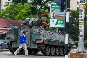 A man walks past an armoured personnel carrier that stations by an intersection as Zimbabwean soldiers regulate traffic in Harare on Nov. 15, 2017. (Credit: AFP / Getty Images)