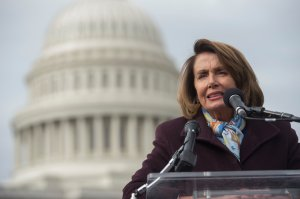 U.S. House Democratic Leader Nancy Pelosi speaks to demonstrators as they protest against the Republican tax reform plan on Capitol Hill, Nov. 15, 2017. (Credit: Saul Loeb / AFP / Getty Images)