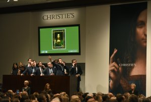 "Christie's employees take bids for Leonardo da Vincis ""Salvator Mundi"" at Christie's New York on November 15, 2017. A 500-year-old work of art depicting Jesus Christ, believed to be the work of Renaissance master Leonardo da Vinci, sold in New York $450.3 million setting a new art auction record, Christie's said. (Credit: Timothy A. Clary/AFP/Getty Images)"