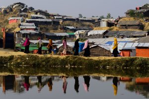 Rohingya refugees are reflected on a pond as they walk back to their homes at Balukhali refugee camp in the Bangladeshi district of Ukhia on Nov. 22, 2017. (Credit: Munir Uz Zaman / AFP / Getty Images)