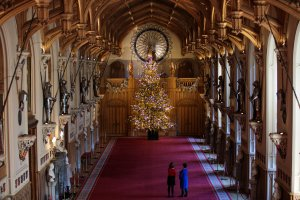 Employees pose with a 20-foot Nordmann Fir tree in St. George's Hall, which has been decorated for the Christmas, on Nov. 23, 2017, in Windsor Castle, England. (Credit: Jack Taylor / Getty Images)