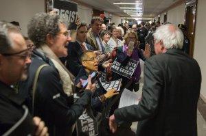 Demonstrators greet Sen. Bernie Sanders on his way to the full committee markup of the FY2018 Reconciliation Legislation on Nov. 28, 2017, in Washington, DC. (Credit: Tasos Katopodis / Getty Images)