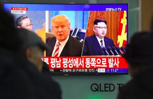 People watch a television news screen showing pictures of U.S. President Donald Trump and North Korean leader Kim Jong-Un at a railway station in Seoul on Nov. 29, 2017. (Credit: JUNG YEON-JE/AFP/Getty Images)