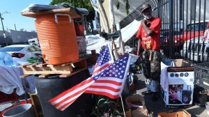 Flags are hoisted at the street-corner encampment of L.A. homeless veteran Kendrick Bailey. (Frederic J. Brown / AFP/Getty Images)