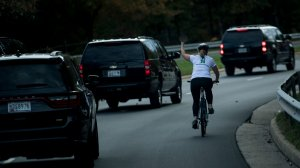 A woman on a bike gestures with her middle finger as a motorcade with US President Donald Trump departs Trump National Golf Course October 28, 2017 in Sterling, Virginia. (Credit: BRENDAN SMIALOWSKI/AFP/Getty Images)