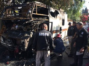 Fire investigators examine the shell of a burned RV after a fatal fire Nov. 20, 2017, in Rancho Park in a photo tweeted by LAFD's Erik Scott.