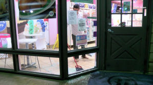 A worker at the Baskin-Robbins location on Arrow Highway in San Dimas is seen sweeping up shards of glass after the location was robbed on Nov. 2, 2017. (Credit: RMG News)