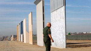 Mario Villarreal, the field office division chief for Customs and Border Protection, walks near the border wall prototypes that were built east of San Ysidro on the border of Mexico, shown here on Nov. 20, 2017. (Credit: K.C. Alfred / San Diego Union-Tribune)