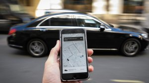 A photo illustration shows a phone displaying the Uber ride-hailing app on Sept. 22, 2017, in London, England. (Credit: Leon Neal/Getty Images)