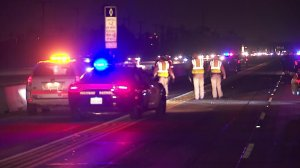 Authorities investigate a fatal crash on the 405 Freeway in Westminster on Dec. 20, 2017. (Credit: KTLA)