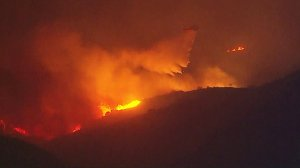 A firefighting helicopter is seen above the Creek Fire on Dec. 5, 2017. (Credit: KTLA)