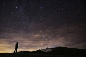A photographer looks at the sky at night to see the annual Geminid meteor shower on the Elva Hill in northern Italy, Dec. 12, 2015. (Credit: Marco Bertorello / AFP / Getty Images)