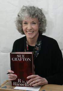 """Author Sue Grafton poses with a copy of her book """"R is for Ricochet"""" at the 10th annual Los Angeles Times Festival of Books at UCLA on April 23, 2005 in Los Angeles. (Credit: Michael Buckner/Getty Images)"""