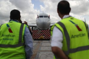 Employees watch as American Airlines Flight 903 prepares for takeoff, becoming the first commercial flight from Miami to Cuba in 55-years on Sept. 7, 2016. (Credit: Joe Raedle / Getty Images)