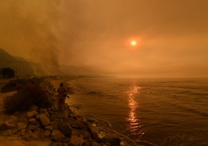 Heavy smoke covers the seaside enclave of Mondos Beach beside the 101 highway as flames reach the coast during the Thomas Fire near Ventura, on Dec. 6, 2017. (Credit: Mark Ralston/AFP/Getty Images)
