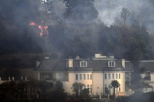 Flames are seen behind a Bel Air mansion threatened by the Skirball Fire on Dec. 6, 2017. (Credit: AFP PHOTO / Robyn Beck)