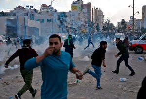 Palestinian protesters run for cover from tear gas during clashes with Israeli troops near the West Bank city of Ramallah at a Dec. 7, 2017, protest against President Donald Trump's decision to recognize Jerusalem as the capital of Israel. (Credit: AFP PHOTO / ABBAS MOMANI)