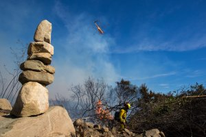 Firefighters cut a fire line near stacked rocks at the Thomas Fire on December 7, 2017 near Fillmore. (Credit: David McNew/Getty Images)