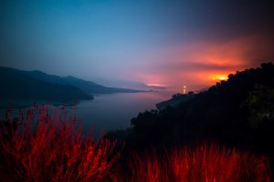 The Thomas Fire burns a hillside behind Lake Casitas near Ventura on Dec. 8, 2017. (Credit: KYLE GRILLOT/AFP/Getty Images)