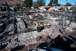 Firefighter Dean Wilson looks for hot spots in the remains of dozens of homes destroyed by the Lilac Fire at a retirement community in Fallbrook, Dec. 8, 2017. (Credit: AFP PHOTO / Robyn Beck)
