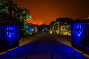 The glow of approaching flames is seen at the gates of an expensive home in Montecito as the Thomas Fire continues to grow on Dec. 12, 2017. (Credit: David McNew / Getty Images)