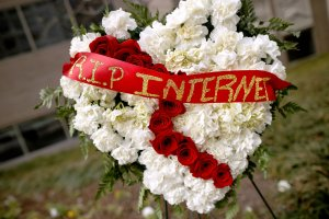 A funeral flower arrangement is set up outside the Federal Communication Commission building during protest against the end of net neutrality rules, Dec. 14, 2017 in Washington, DC. (Credit: Chip Somodevilla / Getty Images)