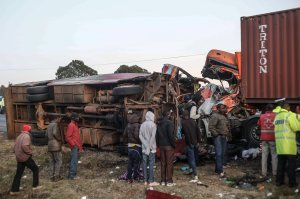 People look at the wreckage of a bus and a lorry that crashed in a head-on collision, killing thirty people near Nakuru, Kenya, on Dec. 31, 2017. (Credit: STR/AFP/Getty Images)
