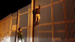 An undated photo shows Border Patrol Agent Eduardo Olmos apprehending a Mexican immigrant trying to cross the U.S.-Mexico border in San Diego. (Gary Coronado / Los Angeles Times)