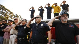 Emergency responders salute as a procession is held for fallen firefighter Cory Iverson in the Fillmore area. (Credit: Al Seib/Los Angeles Times)