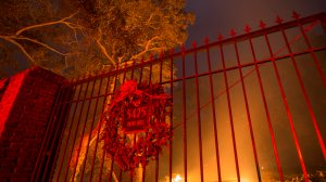 A wreath hangs on the gate of a burned property at the Lilac Fire in the early morning hours of Dec. 8, 2017, near Bonsall in San Diego County. (Credit: David McNew/Getty Images)