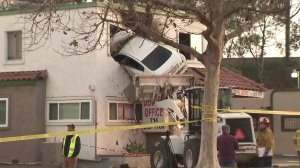 A car remains lodged inside the second floor of a Santa Ana dentist office after the driver crashed into the building on Jan. 14, 2018. (Credit: KTLA)