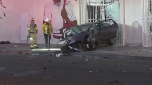 First responders look at a vehicle involved in a crash on Jan. 1, 2018, in the Fairfax district. (Credit: KTLA)