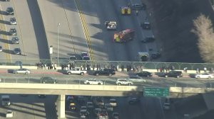People stop on an overpass to survey the damage below on the 210 Freeway. (Credit: KTLA)
