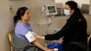 Marenna Bielman, right, takes Angelica Lara's blood pressure as she is treated for flu-like symptoms at St. Joseph Hospital in Orange. (Credit: Allen J. Schaben / Los Angeles Times)