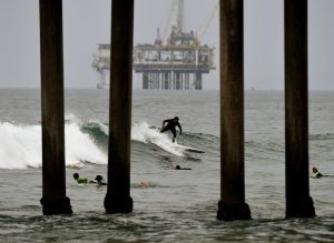 Surfers ride waves in front of an oil rig off Huntington Beach on July 31, 2015. (Credit: Mark Ralston / AFP / Getty Images)