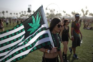 A woman carries a flag bearing marijuana leaves at the Coachella Valley Music & Arts Festival in Indio on April 12, 2014. (Credit: David McNew / AFP / Getty Images)