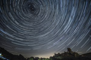 In this composite image, satellites, planes and comets transit across the night sky under stars that appear to rotate above Corfe Castle in the United Kingdom on Aug. 12, 2016. (Credit: Dan Kitwood / Getty Images)