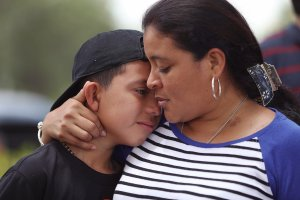 Jenny Martinez hugs her son, William Martinez, as they talk to the media about her trip from El Salvador and her need for asylum in America because of domestic violence and her fear for her life as they join with protesters in front of the United States Citizenship and Immigration Services building in Miramar, Florida, on May 19, 2017. (Credit: Joe Raedle / Getty Images)